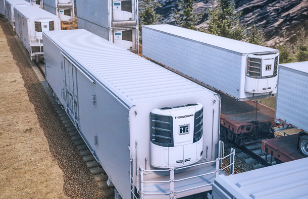 Photo of several trailers on rail cars with Thermo King units on the trailers.