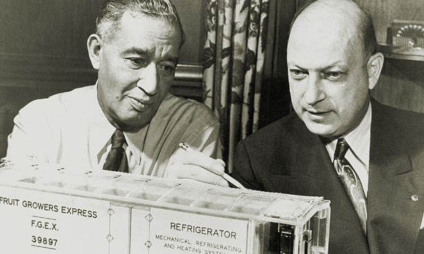 Vintage photo of Fred Jones and Joe Numero examning a model rail car.