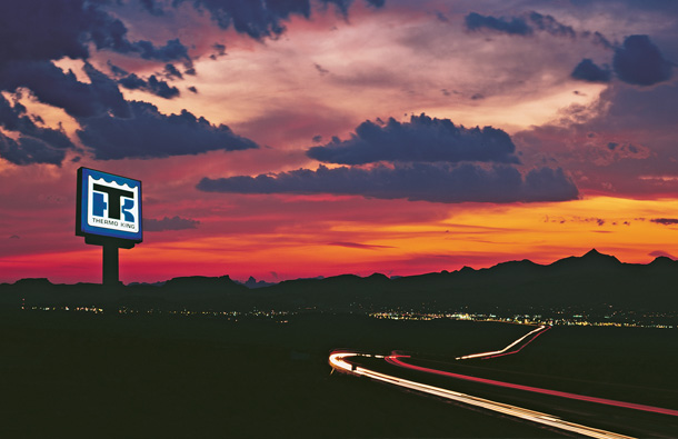 Photo at twilight of a Thermo King dealer sign lit up against the sunset and mountains.